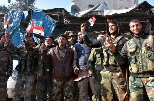 Des soldats du régime agitent des drapeaux syriens avec le portrait d'Assad dans le quartier de Bab al-Nairab à Alep le 10 décembre 2016 © George OURFALIAN AFP