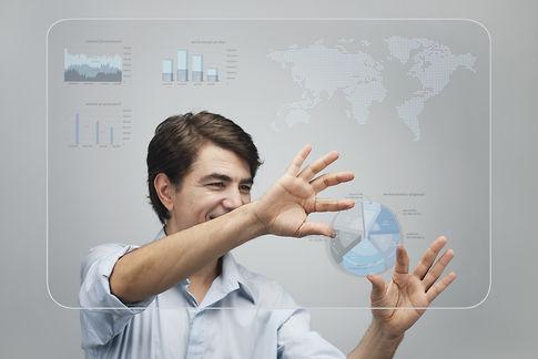 Businessman using advanced touch screen technology to view sales data ©Milena Boniek