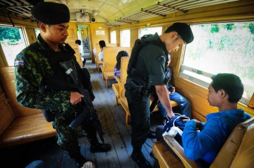 Des soldats controlent les passagers du train de 12H33, le 21 novembre 2016 à Narathiwat dans l'extrême sud de la Thaïlande © MADAREE TOHLALA AFP