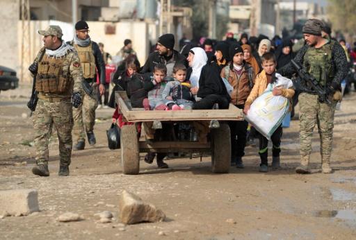 Des soldats irakiens évacuent les civils fuyant Al-Intisar, le quartier oriental de Mossoul, le 31 décembre 2016, lors d'une opération militaire contre les djihadistes de l'EI © AHMAD AL-RUBAYE AFP