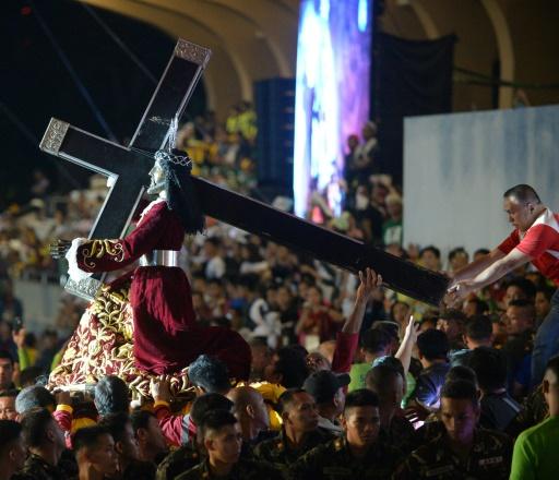 """Une foule de Philippins se rassemblent à Manille pour la procession du """"Nazaréen noir"""", le 9 janvier 2017 et tenter de toucher la statue du Christ © TED ALJIBE AFP"""