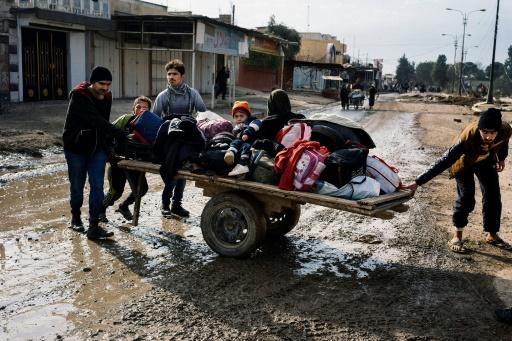 Des Irakiens fuient leurs habitations et sortent leurs effets personnels dans les rues de Mossoul, lors d'une opération militaire, le 8 janvier 2017 © Dimitar DILKOFF AFP