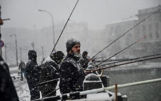 Des pêcheurs sur le pont Galata, à Istanbul, durant la tempête de neige, le 8 janvier 2017 © BULENT KILIC AFP