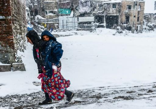 Une Syrienne et son enfant sous la neige à Istanbul le 8 janvier 2017 © YASIN AKGUL AFP