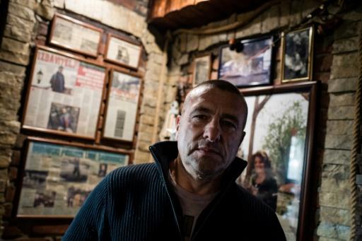 Renato Grbic, pêcheur, restaurateur et à l'occasion sauveur du Danube, posent devant des articles de journaux relatant ses sauvetages de suicidés, le 21 décembre 2016 à Belgrade © ANDREJ ISAKOVIC AFP