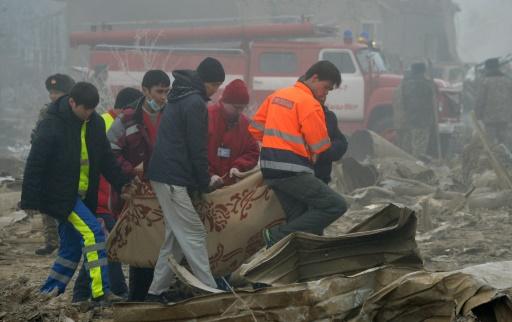 Des sauveteurs évacuent le corps d'une victime du crash d'un avion-cargo turc sur des habitations, le 16 janvier 2017  près de l'aéroport de Bichkek, au Kirghizstan  © Vyacheslav OSELEDKO AFP