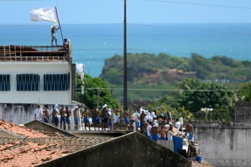 Un groupe de prisonniers déployant des drapeaux sur le toit délabré du plus grand centre pénitencier de l'État de Rio Grande do Norte, le 16 janvier 2017. © ANDRESSA ANHOLETE AFP