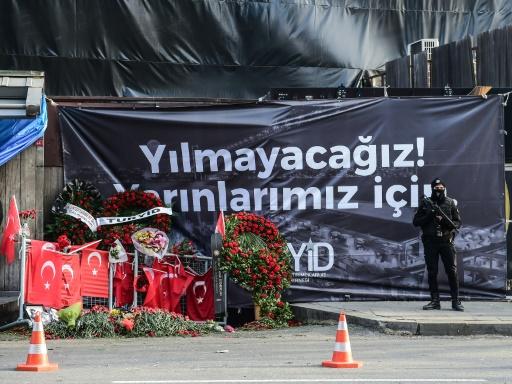 """Un policier turc anti-émeute devant une banderole """"pour notre avenir nous n'allons pas plier"""" déployée  le 3 janvier 2017 à Istanbul devant la discothèque Reina  © YASIN AKGUL AFP"""