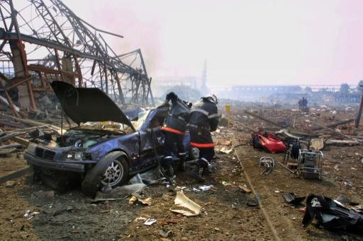 Des pompiers essaient de sortir une victime de son véhicule sur le site de l'usine chimique AZF à Toulouse après l'explosion le 21 septembre 2001  © ERIC CABANIS AFP/Archives