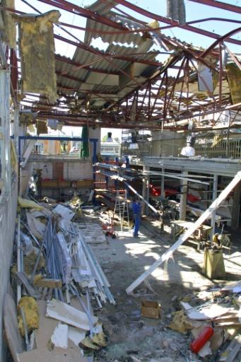 Un ouvrier enlève des cylindres, le 26 septembre 2001 à Toulouse, dans le local sérieusement endommagé d'une entreprise située près du lieu où s'est produite, le 21 septembre, l'explosion de l'usine chimique AZF © PASCAL PAVANI AFP/Archives