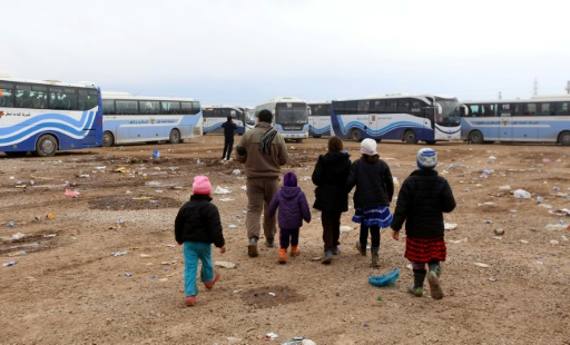 Des Iraquiens déplacés, qui avaient fui les violences autour de Mossoul, rassemblent leurs biens avant d'embarquer dans un autobus dans le camp de réfugiés d'al-Khazer, à environ 40 kilomètres à l'est d'Arbil, le 25 janvier 2017 © SAFIN HAMED AFP