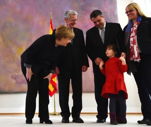 La chancelière Angela Merkel (g) s'adresse à la fille du nouveau chef de la diplomatie allemande Sigmar Gabriel (2e d), Marie, en présence du président Joachim Gauck (2e g) et l'épouse de M. Gabriel, Anke (d), à Berlin, le 27 janvier 2017 © Tobias SCHWARZ                      AFP