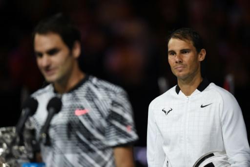 Rafael Nadal (d) écoute le discours de Roger Federer, vainqueur de l'Open d'Australie au détriment de l'Espagnol, le 29 janvier 2017 à Melbourne © PAUL CROCK                      AFP