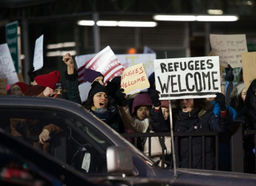 """Des opposants aux décrets sur l'immigration de Donald Trump manifestent à l'aéroport JFK de New York le 28 janvier 2017 avec des pancartes disant """"Bienvenue aux réfugiés"""" © Bryan R. Smith AFP/Archives"""