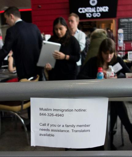 """Ecriteau le 30 janvier 2017 à l'aéroport JFK, disant """"Ligne d'urgence pour l'immigration musulmane: appelez si vous ou un membre de votre famille a besoin d'assistance. Interprètes disponibles""""   © Don EMMERT AFP"""