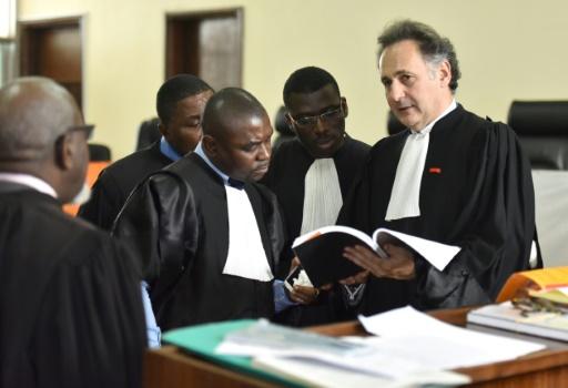 Maître Pierre Olivier Sur (D), l'un des avocats français des familles des victimes, parle avec Maître Ange Rodrigue Dadjé, l'un des avocats de la défense et du général Dogbo Blé, avant le début des audiences, le 31 janvier 2017 à Abidjan © Sia KAMBOU AFP