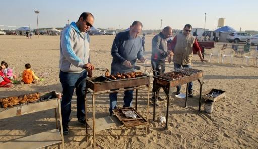 Des hommes préparent un barbecue dans un campement pour l'hiver, le 13 janvier 2017 à Al-Julaiaa, au Koweït © Yasser Al-Zayyat AFP