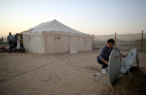 Un membre de la famille d'Ahmad al-Shimmari installe des antennes satellite au campement d'hiver d'Al-Julaiaa, le 13 janvier 2017 au Koweït © Yasser Al-Zayyat AFP