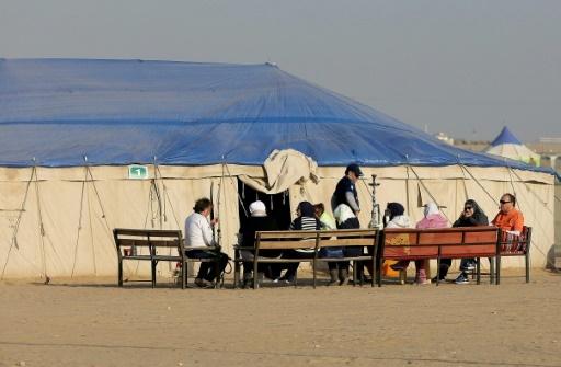 Une famille prend le frais devant sa tente au campement d'hiver d'Al-Julaiaa, le 13 janvier 2017 au Koweït © Yasser Al-Zayyat AFP