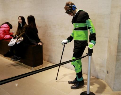 Un homme portant une combinaison de simulation du vieillissement au Musée du Louvre à Paris le 27 janvier 2017 © JACQUES DEMARTHON AFP