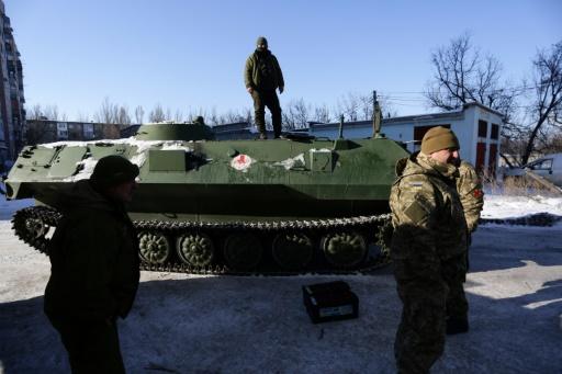 Un auxiliaire sanitaire se tient debout sur un véhicule blindé de transport de troupes le 30 janvier 2017 à Donetsk après avoir déposé un militaire blessé à l'hôpital d'Avdiivka © Aleksey FILIPPOV AFP