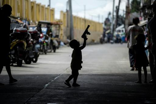 Un enfant joue avec l'arme d'un policier à Manille le 6 octobre 2016 © NOEL CELIS AFP/Archives