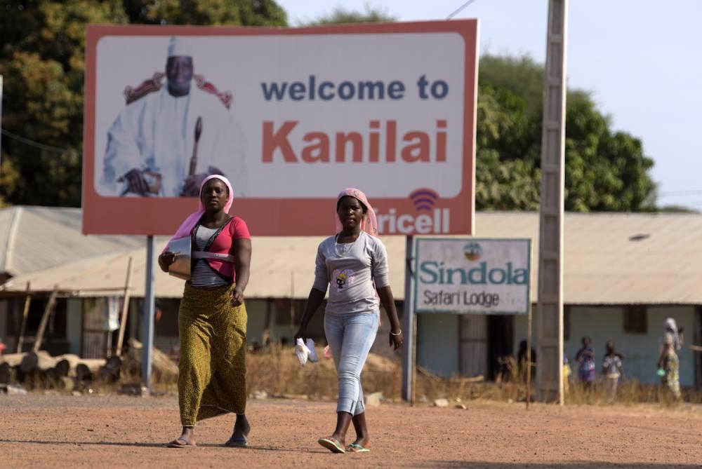 Kanilaï, le village de l'ex-dictateur. Des jeunes femmes passent devant un grand panneau avec un portrait de Jammeh. © SEYLLOU SEYLLOU / AFP