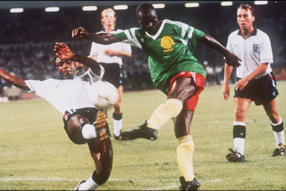 1er juillet 1990 : quatre ans après la CAN 1986 du Caire, à 38 ans, Milla assure encore lors de la Coupe du monde  en Italie. Ici à Naples contre l'Angleterre face au défenseur anglais Paul Parker.  ©  DPA/AFP