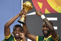 Le capitaine des Lions indomptables, Benjamin Moukandjo (à gauche), et Nicolas Nkoulou, auteur du but égalisateur, soulèvent la Coupe d'Afrique des nations que le Cameroun vient de remporter face à l'Égypte ce 5 février 2017 à Libreville.