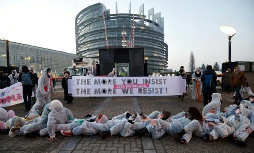 """Des opposants au CETA son couchés devant le Parlement européen à Strasbourg le 15 février 2017 avec une banderole clamant""""plus vous insistez, plus nous résistons"""" © FREDERICK FLORIN AFP"""