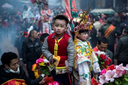 Des enfants, maquillés et habillés de costumes bordés et colorés, en parade, debout sur des palanquins, dans les rues de Tufang, le 11 février 2017 dans l'est de la Chine © Johannes EISELE AFP