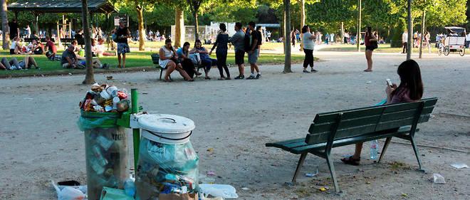 Au Champs-de-Mars, à Paris, des poubelles qui débordent et des sols maculés de déchets.