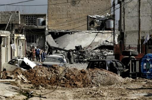 Des habitants au milieu d'un quartier en ruines le 1er mars 2017 à Mossoul © ARIS MESSINIS AFP
