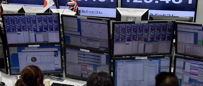 """Traders ckeck computer screens showing the Japanese yen rate against the British pound at a brokerage in Tokyo on October 7, 2016.The pound suffered a """"flash crash"""" in Asia on a computer-generated sell-off in the beleaguered currency, as tough talk from French President Francois Hollande underscored the perils ahead for Brexit-bound Britain. / AFP PHOTO / TORU YAMANAKA"""