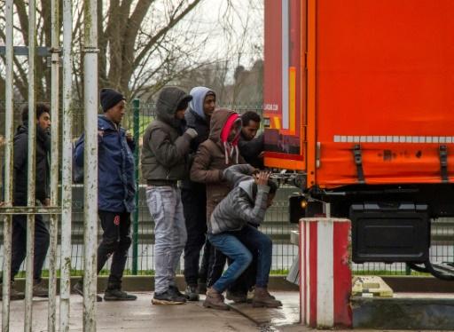 Des migrants ouvrent les portes d'un semi-remorque à une station service sur l'autoroute A25 à Steenvoorde, le 28 février 2017 © PHILIPPE HUGUEN AFP