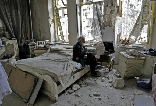 Mohamed Mohiedine Anis, 70 ans, fume la pipe et écoute de la musique sur son gramophone dans sa chambre à coucher détruite par des bombardements, le 9 mars 2017 à Alep dans le quartier autrefois rebelle de Chaar © JOSEPH EID AFP