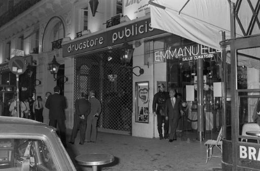 Des enquêteurs à l'entrée du  drugstore Publicis, cible d'un attentat le 15 septembre 1974 à Paris © STF AFP