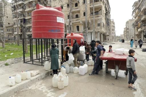 Des habitants viennent remplir leurs bidons d'eau dans une rue de l'ancien quartier rebelle de Chaar, le 9 mars 2017 à Alep, en Syrie © JOSEPH EID AFP