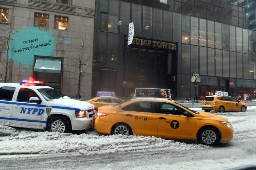 Une voiture de police pousse un taxi embourbé dans la neige, à New York, devant la Trump Tower, le 14 mars 2017 © Jewel SAMAD AFP