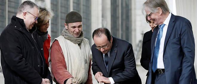 Le 11 mars, Francois Hollande grave ses initiales sur une pierre à Saint-Denis (93). Autour de lui, le maire de la ville, Laurent Russier (à gauche), Valérié Pécresse (2e à gauche),Patrick Braouezec (à droite) et Audrey Azoulay (2e à droite)