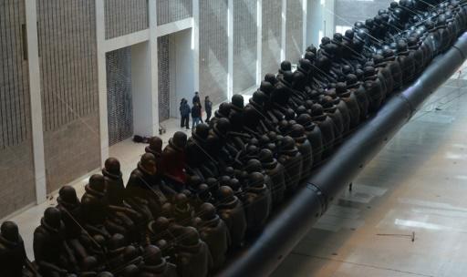 """L'installation géante de l'artiste dissident chinois Ai Weiwei """"La Loi du Voyage"""", un canot pneumatique de 70 mètres avec à son bord 258 statues de réfugiés, illustrant la crise migratoire, exposée le 16 mars 2017 à Prague, en République Tchèque © Michal Cizek AFP"""