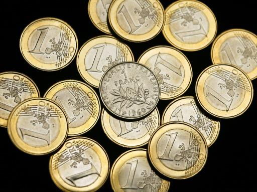 Une pièce de 1 franc entourée de pièces de 1 euro, le 31 décembre 2001 à Paris © PATRICK KOVARIK AFP/Archives