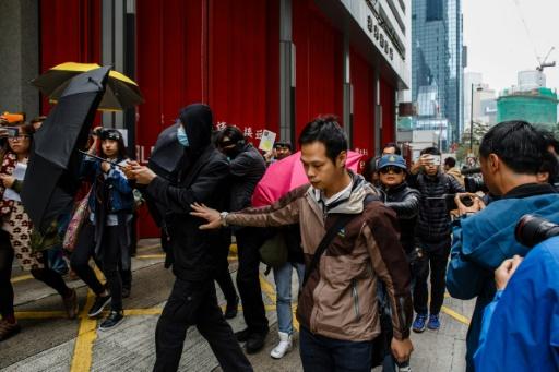 Des militants couvrent leurs visages avec des parapluies en quittant le tribunal de Hong Kong, le 17 mars 2017 © Anthony WALLACE AFP