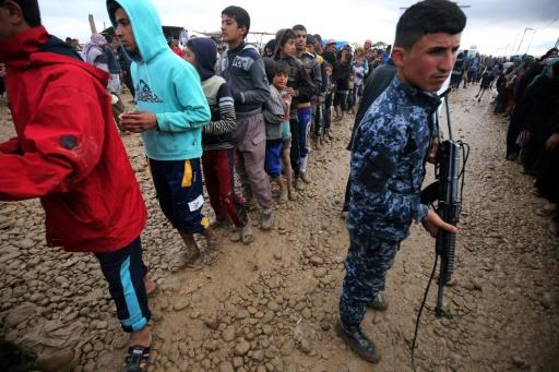 Des Iraquiens déplacés de Mossoul font la queue pour recevoir des rations d'aide au camp de Hammam al-Alil, au sud de Mossoul, le 16 mars 2017 © AHMAD AL-RUBAYE AFP