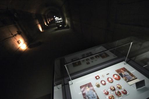 """Des photos et des badges à l'effigie de l'ancien leader chinois Mao Tsé-toung exposés, le 21 février 2017, à la """"centrale 816"""", une ancienne base secrète creusée sous les montagnes chinoises censée fabriquer du plutonium pour la bombe atomique  © WANG ZHAO AFP"""