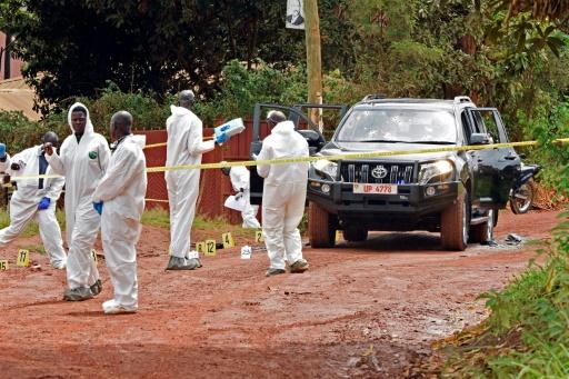 Des experts en médecine légale enquêtent sur la scène de crime du porte-parole de la police ougandaise Andrew Kaweesi, dans un faubourg de Kampala, le 17 mars 2017 © ISAAC KASAMANI AFP