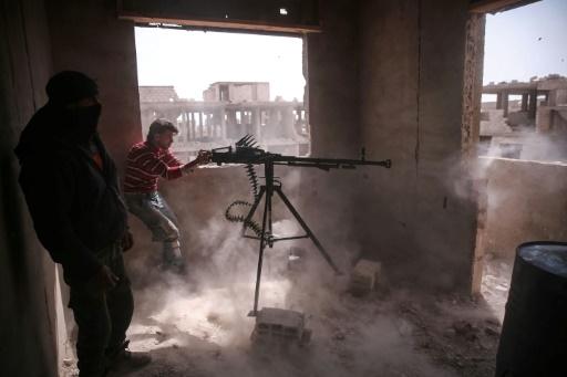 Des combattants rebelles du groupe Faylaq al-Rahman tirent à la mitrailleuse dans le quartier de Jobar, le 19 mars 2017 dans la partie est de Damas en Syrie © AMER ALMOHIBANY AFP