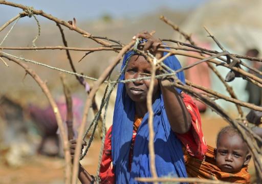 Une femme, son enfant attaché sur son dos, assemble des branchages pour construire une hutte dans un camp de familles déplacées à Baidoa, le 14 mars 2017, dans le sud-ouest de la Somalie © TONY KARUMBA AFP