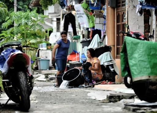 """Des habitants du """"kampung"""" de Tongkol à Jakarta, lavent leurs vêtements devant chez eux, le 31 janvier 2017 © Bay ISMOYO AFP/Archives"""