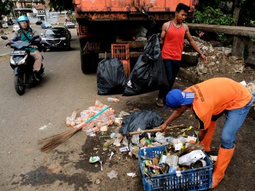 Des ouvriers chargés d'enlever les ordures ménagères collectent des déchets plastiques à Jakarta le 27 janvier 2017 © Bay ISMOYO AFP/Archives